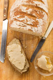 Slice of freshly baked floured country bread with butter Royalty Free Stock Image