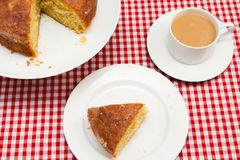 Homemade lemon drizzle cake. A slice of freshly made lemon drizzle cake with a cup of coffee royalty free stock photo