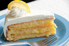 Slice of frosted lemon cake on a blue plate Stock Photos