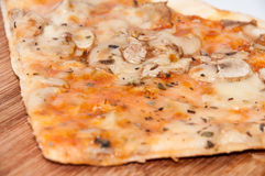Slice of funghi pizza on the wooden board.  Royalty Free Stock Images