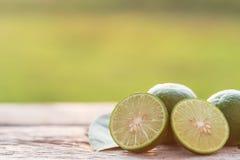 Slice green fresh lemon on wooden table background Royalty Free Stock Images