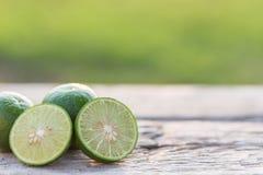 Slice green fresh lemon on wooden table background Royalty Free Stock Photos