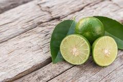 Slice green fresh lemon on wooden table background Royalty Free Stock Image