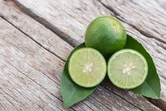 Slice green fresh lemon on wooden table background Stock Image