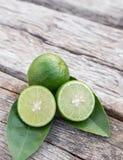 Slice green fresh lemon on wooden table background Stock Photo