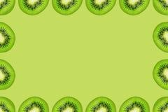 Slice of green raw kiwi fruit background, frame and border, empty space.  royalty free stock image