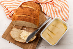Slice home baked bread with margarine on a cutting board Stock Photography