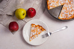 Slice of homemade apple pie with fork and fresh apples on light Stock Images