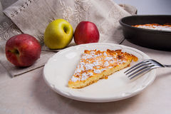 Slice of homemade apple pie with fork and fresh apples on light Royalty Free Stock Photo