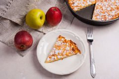 Slice of homemade apple pie with fork and fresh apples on light Stock Image