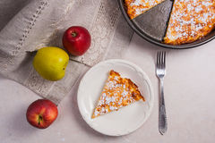 Slice of homemade apple pie with fork and fresh apples on light Royalty Free Stock Image