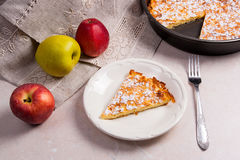 Slice of homemade apple pie with fork and fresh apples on light Stock Photo