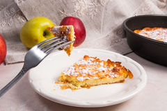 Slice of homemade apple pie and fork on light marble background Royalty Free Stock Images