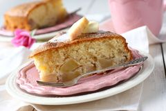 Slice of homemade apple sponge cake on pink plate Stock Photo