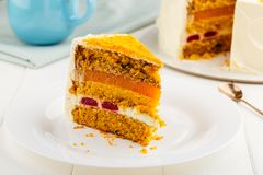 Slice of homemade carrot cake with walnuts, cream cheese and jel. Ly on white plate Stock Image