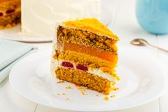 Slice of homemade carrot cake with walnuts, cream cheese and jel. Ly on white plate Royalty Free Stock Photo