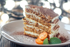 Slice of homemade layered honey cake with mint, kumquat and walnuts, traditional food of Jewish New Near. Sweet food. Slice of homemade layered honey cake with Royalty Free Stock Photo