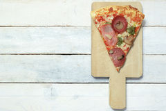 Slice of homemade pizza 4 seasons in a white wooden table Stock Images