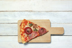 Slice of homemade pizza 4 seasons in a white wooden table Royalty Free Stock Photo