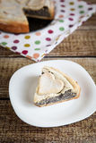 Slice of homemade poppy seed pie with pastry hearts. Slice of homemade poppy seed and custard pie with pastry hearts on fabric with color dots Stock Photos