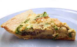 Slice of homemade quiche. Slice of quiche with artichoke and arugula on blue plate Stock Photos