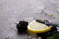 A slice of juicy yellow lemon, blackberries, green leaves of mint and a spoon on a gray blurred background. Royalty Free Stock Images
