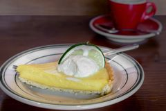 A slice of keylime pie with a cup of coffee stock images