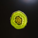 Slice of kiwi in backlight. Green slice of kiwi in backlight with dark background Royalty Free Stock Photography