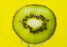 Slice kiwi in bubbles Stock Photography