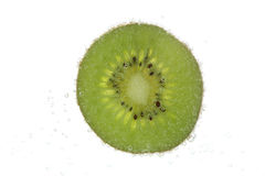 Slice of kiwi in carbonated water isolated Stock Images