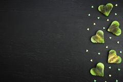 Slice of kiwi fruit on black background. Flat lay, top view. Heart symbol of fruits Stock Image