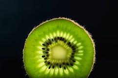 Slice of kiwi fruit on black background horizontal. space for te Stock Photography