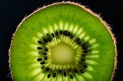 Slice of kiwi fruit close-up on black background horizontal Stock Images