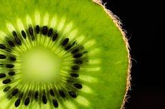 Slice of kiwi fruit close-up on black background horizontal. spa Royalty Free Stock Images