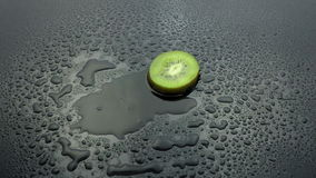 Slice kiwi fruit falling on wet stock footage