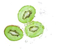 Slice of kiwi splash on water isolated Royalty Free Stock Photography