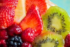 Slice kiwi and a variety of fresh fruits in sweet gelatin. Berries close-up in soft focus. Delicious dessert. royalty free stock images