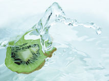 Slice of kiwifruit dipped in water Stock Photography