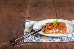 A slice of lasagna on a wood table stock photos