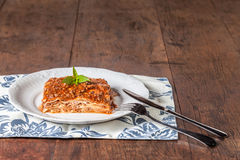 A slice of lasagna on a wood table stock image