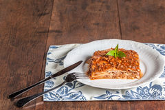 A slice of lasagna on a wood table stock photo