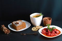 Slice of layered honey cake decorated with anise star, dessert fork, mint, dried lemons, sticks of cinnamon, strawberry jam, cocoa Royalty Free Stock Images