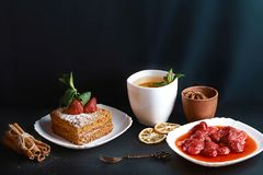 Slice of layered honey cake decorated with anise star, dessert fork, mint, dried lemons, sticks of cinnamon, strawberry jam, cocoa Royalty Free Stock Photo