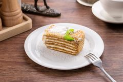 Slice of layered honey cake with mint leaves on wooden table. Side view stock photography
