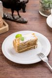 Slice of layered honey cake with mint leaves on wooden table. Side view royalty free stock image
