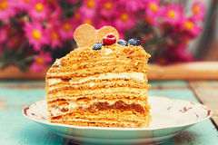 Slice of layered honey cake. On rustic wooden background. Homemade baking Royalty Free Stock Photos