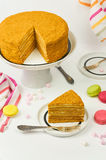 Slice of layered honey cake. Sweet homemade medovik cake on a white table. Selective focus Stock Photography