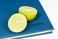 Slice of lemon on blue diary. Of year 2016 Royalty Free Stock Photos