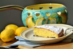 Slice of lemon cake on cake server. With lemons in the background Stock Image