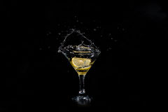 A slice of lemon dropped in a glass of cocktail Stock Image